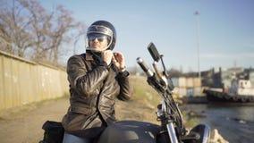 O motociclista caucasiano do homem veste um capacete perto do porto no dia ensolarado frio vídeos de arquivo