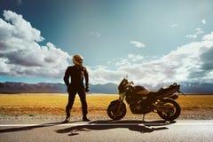 O motociclista com motocicleta está na estrada Fotografia de Stock