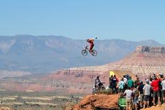 O motociclista da montanha salta relógios do penhasco e da multidão Imagem de Stock