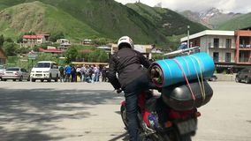 O motociclista da mulher senta-se na motocicleta, turismo do curso, no meio das montanhas de Geórgia, opinião do kazbek filme