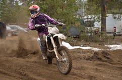 O motociclista deixa a trilha com uma grande pena da areia imagens de stock royalty free