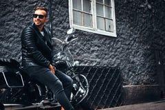 O motociclista elegante vestiu-se em um casaco de cabedal preto e nas calças de brim que sentam-se em sua motocicleta retro em um imagem de stock royalty free