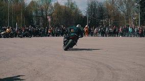 O motociclista executa uma tração bonita em um círculo na exposição automóvel Uma multidão de espectadores que olham a mostra da  vídeos de arquivo
