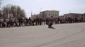 O motociclista gerencie a bicicleta em torno de sua linha central que deixa traços de pneus no pavimento Playback lento filme