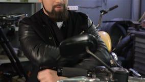 O motociclista masculino cruza seus braços em sua caixa na motocicleta filme