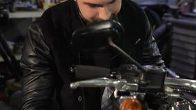 O motociclista masculino limpa o painel da motocicleta filme