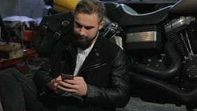 O motociclista masculino usa seu telefone perto do interruptor inversor na oficina da motocicleta filme