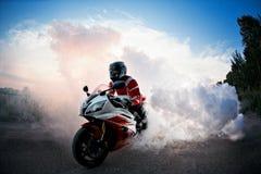 O motociclista que fica na estrada da bicicleta com fumo do pneu, queima-se na mostra do moto O por do sol foto de stock royalty free