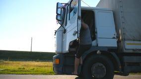 O motorista abre a porta e retira o caminhão estacionado O homem está andando perto do carro Caminhão estacionado no campo video estoque