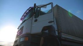 O motorista abre a porta e senta-se para baixo no caminhão estacionado Paisagem bonita no fundo Caminhão estacionado no campo vídeos de arquivo