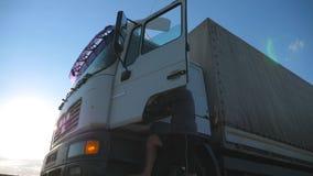 O motorista abre a porta e senta-se para baixo no caminhão estacionado Paisagem bonita no fundo Caminhão parado no campo filme