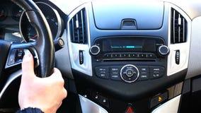 O motorista ajusta o nível do volume do sistema acústico do ` s do carro no volante vídeos de arquivo