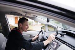 O motorista ajusta o navegador de GPS que senta-se atrás da roda Imagens de Stock Royalty Free
