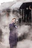 O motorista britânico do trem do vapor bebe a água em Nene Valley Railway fotografia de stock