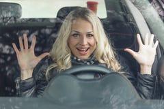 O motorista da mulher senta-se no carro preto Imagem de Stock