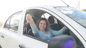 O motorista feliz da jovem mulher que guarda o carro fecha a condução de seu carro novo video estoque