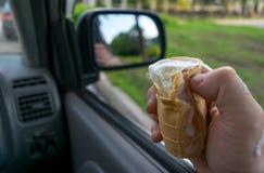 O motorista guarda o gelado ao conduzir um carro Fotos de Stock
