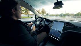 O motorista masculino trabalha com um telefone, sentando-se em um carro no piloto automático, fim acima vídeos de arquivo