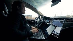 O motorista monta um carro no piloto automático ao trabalhar com um portátil, fim acima vídeos de arquivo