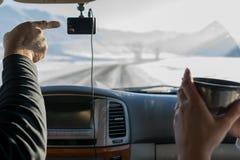 O motorista, mostra a menina com uma caneca de chá, o sentido da estrada, no inverno, no mountai coberto de neve imagem de stock