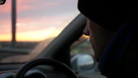 O motorista no tampão monta atrás da roda do carro para encontrar o por do sol HD, 1920x1080, movimento lento filme