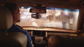O motorista para o carro perto da cara da parada do ônibus e das voltas à câmera video estoque