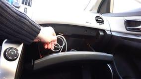 O motorista remove o carregador para o telefone celular do compartimento de luva video estoque