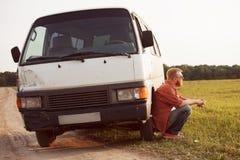 O motorista senta-se ao lado de seu carro imagem de stock royalty free