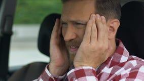 O motorista tem a dor de cabeça após o dia de trabalho ocupado e fatigante, atenção do motorista filme