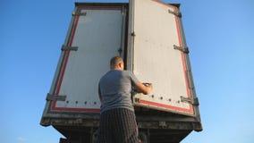 O motorista vem ao caminhão estacionado e abre a porta do reboque no dia ensolarado do verão Caminhão parado no campo fundo video estoque