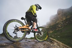 O Mountain bike extremo ostenta o homem do atleta no capacete que monta fora contra um fundo das rochas lifestyle experimentação imagem de stock