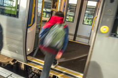 O movimento borrou a porta entrando do trem do menino adolescente Fotografia de Stock Royalty Free