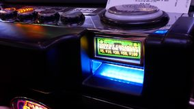 O movimento da mulher introduz o dinheiro no slot machine dentro do casino filme