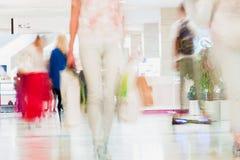 O movimento defocused abstrato borrou os jovens que andam no shopping Figura bonita de uma menina com compra imagens de stock royalty free
