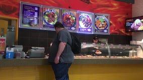 O movimento do alimento da compra do cliente checkout sobre o contador com fumo pesado na praça da alimentação i video estoque