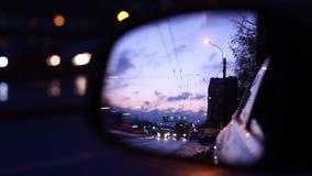 O movimento dos carros na estrada refletiu no espelho de carro video estoque