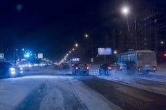 O movimento dos carros na noite da estrada do inverno imagem de stock