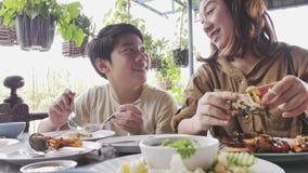 O movimento lento da mãe asiática feliz da família e o filho apreciam comer filme