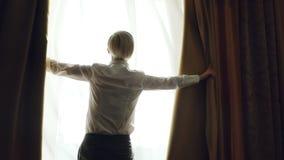 O movimento lento da mulher loura revela cortinas na sala de hotel na manhã e vista na janela