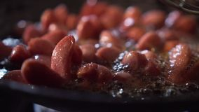 O movimento lento da salsicha pequena obt?m fritado em uma bandeja completamente do ?leo 1 vídeos de arquivo