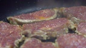 O movimento lento de um cheff está cozinhando um lombinho de carne de porco fritado na bandeja na cozinha filme