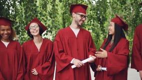 O movimento lento disparado zorra de rir jovens gradua-se guardando os diplomas que estão na linha fora na apreciação do terreno video estoque