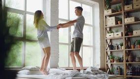 O movimento lento do casal novo que salta e que dança na cama de casal na sala clara com grandes janelas, povos felizes é filme