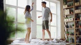 O movimento lento do casal novo que salta e que dança na cama de casal na sala clara com grandes janelas, povos felizes é video estoque