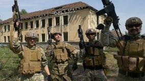 O movimento lento dos soldados team comemorando sua realização da vitória por um acendimento todas suas armas no céu vídeos de arquivo
