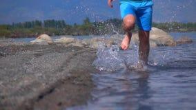 O movimento lento super disparou de homem desconhecido que corre na água pouco profunda para a câmera video estoque