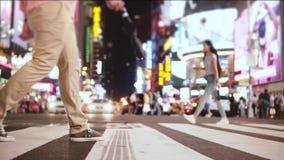 O movimento lento surpreendente de baixo ângulo disparou da multidão que anda através da rua com muitos anúncios na noite no Time filme