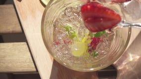 O movimento lento um suco de fruta de refrescamento é derramado em um vidro filme