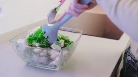 O movimento lento, uma salada em uma bacia de salada de vidro de galinha e as plantas verdes temperaram com molho do sésamo e o g filme