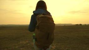 o muchacha que viaja con una mochila contra el cielo y la llamarada de almacen de video